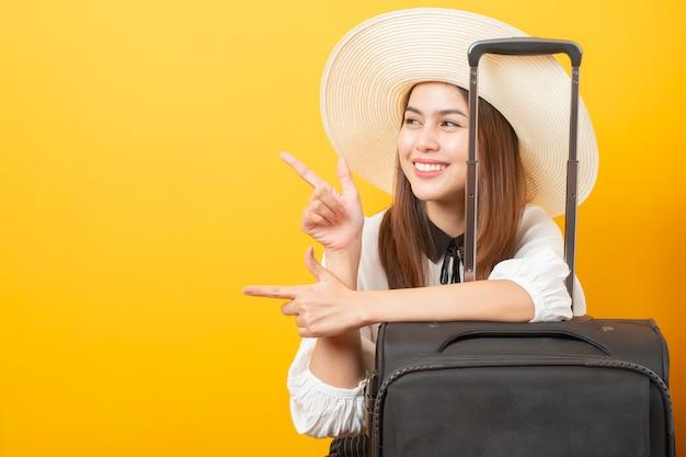 Schöne reisendfrau ist auf gelber wand aufregend