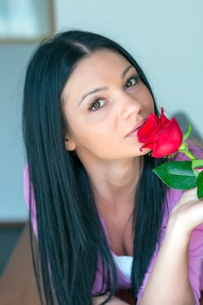 Schöne reizvolle junge frau, die einzelne rose anhält