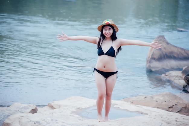 Schöne reizvolle junge frau im bikini am felsen des wasserfalls