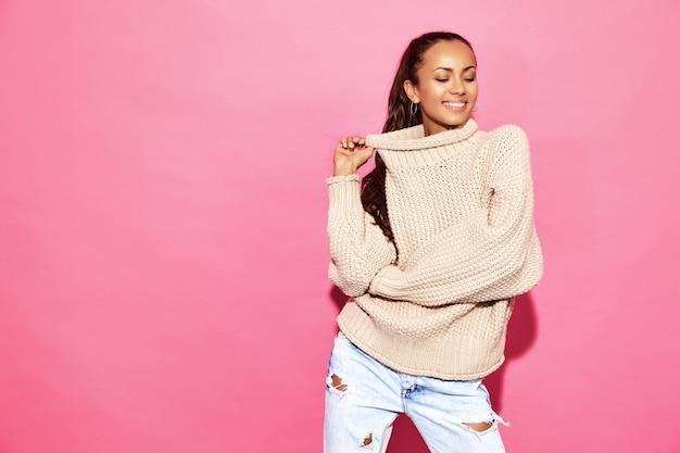 Schöne reizvolle lächelnde herrliche frau. frau, die in der stilvollen weißen strickjacke, auf rosa wand steht. konzept des valentinstags
