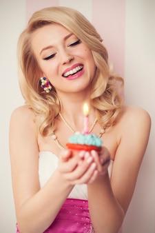 Schöne retro-frau feiern mit blauem muffin