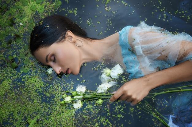 Schöne romantische frau der kunst liegt im sumpf im blauen langen kleid mit blumen. porträt brunette im transparenten kleid in wassersumpf-schlamm-entengrütze. buchcover