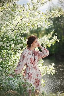 Schöne romantische frau steht in den zweigen des blühenden apfelbaums. frühlingsporträtmädchen im blumenapfelbaum