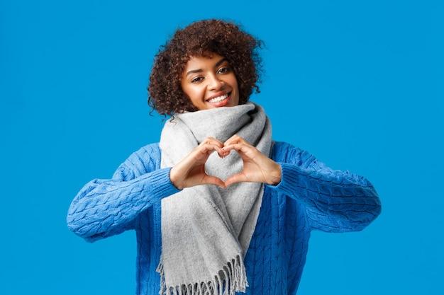 Schöne, romantische fröhliche afroamerikanische freundin mit afro-haarschnitt, neigungskopf, der herzzeichen zeigt, liebe und zuneigung gesteht, winterschal, pullover tragend, über blauer wand stehend.
