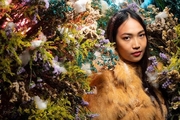Schöne romantische junge asiatische frau im fuchspelzstoff in der buschvielfalt der blumen, die auf hintergrund frische und getrocknete flora aufwerfen. inspiration von herbst winter schnee parfüm, kosmetikkonzept.