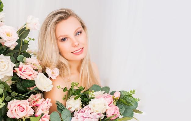 Schöne romantische junge frau mit natürlichem make-up. hellrosa und weiße rosen mit viel grün. parfüm- und kosmetikkonzept.