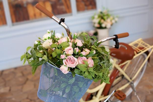 Schöne romantische landschaft: vintage weidenkorb mit blumen in der nähe von café. altes fahrrad mit blumen in einem metallkorb an der wand der bäckerei oder des coffeeshops gegen blaue wand. dekor fahrradblumen