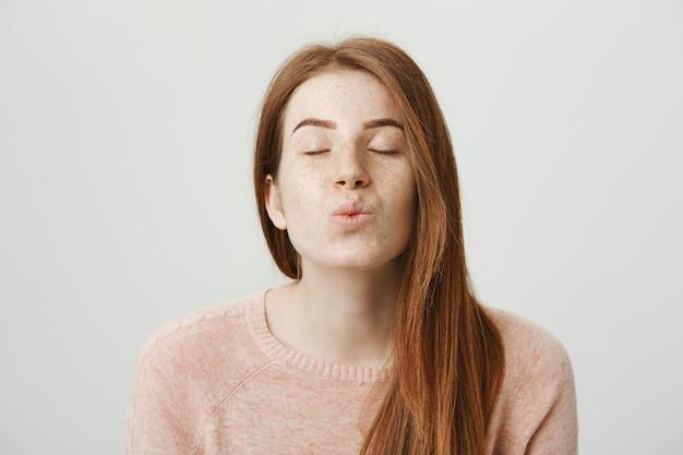 Schöne romantische rothaarige mädchen falten lippen, blasenden kuss