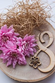 Schöne rosa blumen auf holzscheibe mit nummer acht für 8. märz, internationaler frauentag
