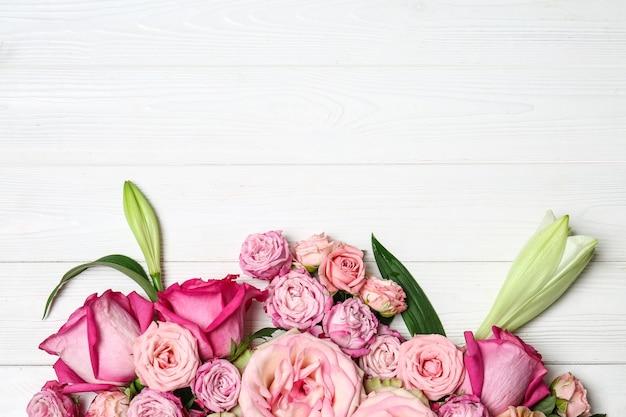 Schöne rosa blumen auf weißem hölzernem hintergrund