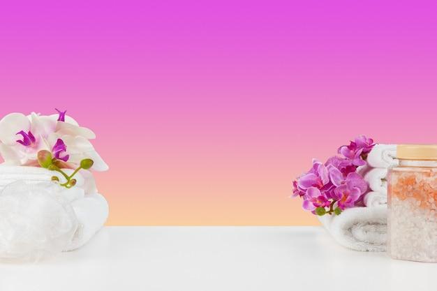 Schöne rosa blumen und weiße handtücher auf rosa hintergrund
