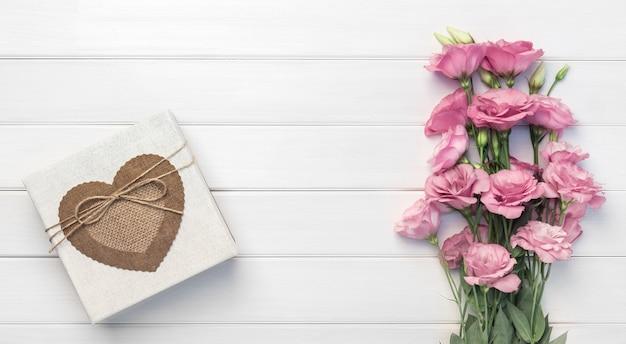 Schöne rosa eustoma blumen und handgemachte geschenkbox auf weißem holzhintergrund. speicherplatz kopieren, draufsicht,