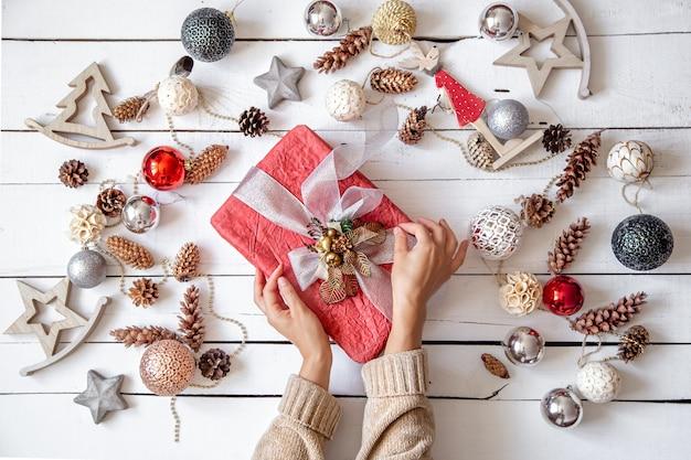 Schöne rosa geschenkbox in den händen gegen die wand der details des weihnachtsdekors schließen oben.
