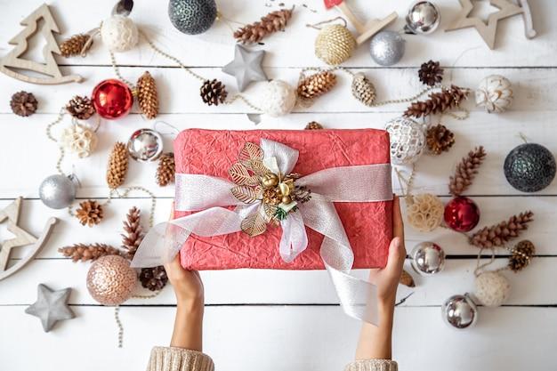 Schöne rosa geschenkbox in den händen vor dem hintergrund der details der weihnachtsdekor-nahaufnahme.