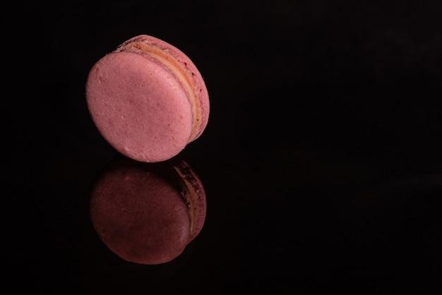 Schöne rosa geschmackvolle makronen auf einem dunklen hintergrund