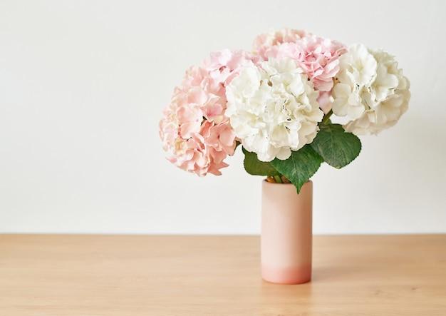 Schöne rosa hortensienblumen in der vase auf tisch.