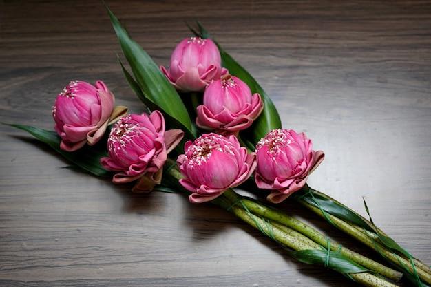 Schöne rosa lotusblume zum beten von buddha auf holzuntergrund