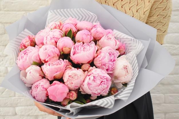 Schöne rosa pfingstrosen der liebe in stilvoller floristischer verpackung.