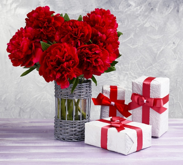 Schöne rosa pfingstrosen und geschenke auf holztisch