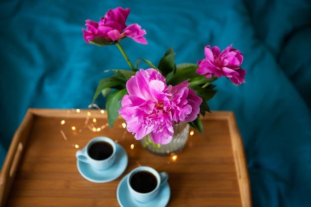 Schöne rosa pfingstrosen und zwei tasse kaffees stehen auf einem hölzernen behälter im bett. nahansicht. sicht von oben.