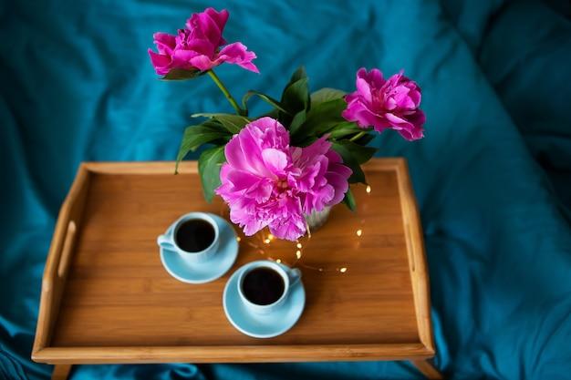 Schöne rosa pfingstrosen und zwei tassen kaffee stehen auf einem holztablett im bett. nahansicht. sicht von oben.