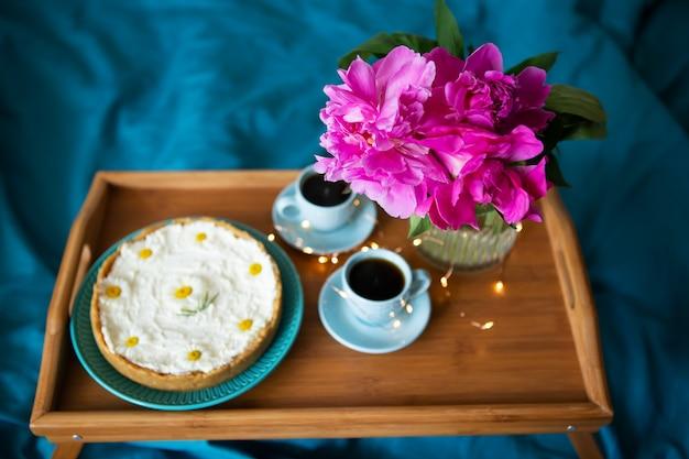 Schöne rosa pfingstrosen und zwei tassen kaffee und pfannkuchen