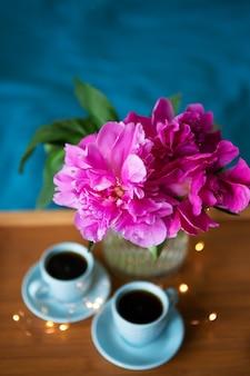 Schöne rosa pfingstrosen und zwei tassen kaffee