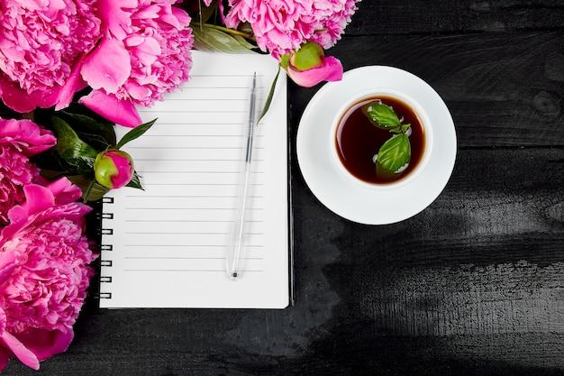 Schöne rosa pfingstrosenblumen mit notizbuch und stift