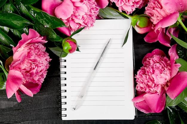 Schöne rosa pfingstrosenblumen und notizbuch, draufsicht