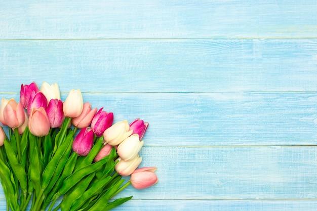 Schöne rosa tulpe blüht auf hölzernem hintergrund des blauen sommers mit kopienraum. ostern- und frühlingsgrußkarte. minimaler stil.