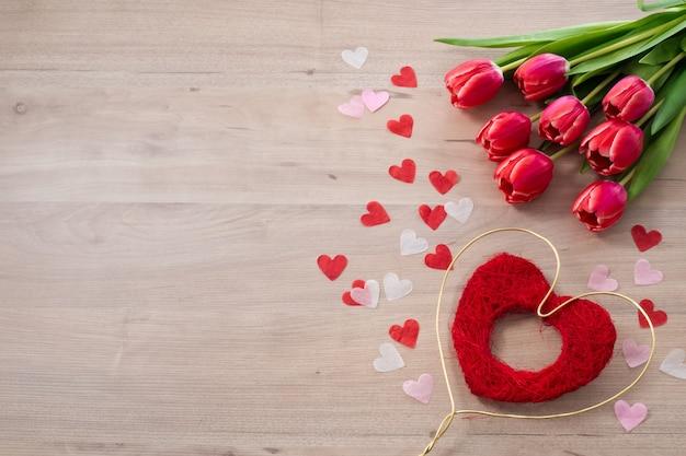 Schöne rosa tulpe mit rotem und goldenem herzen für valentinstag