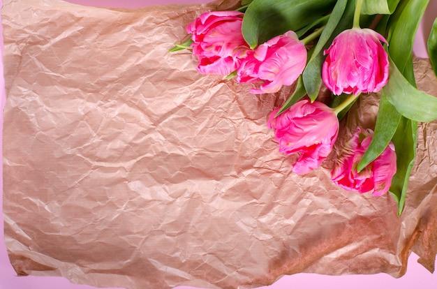 Schöne rosa tulpen im papier auf weinlesepapier.