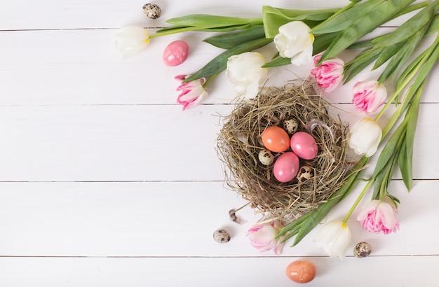 Schöne rosa tulpen mit bunten wachteln und hühnereiern im nest auf weißem holztisch. frühlings- und osterferienkonzept mit kopierraum.