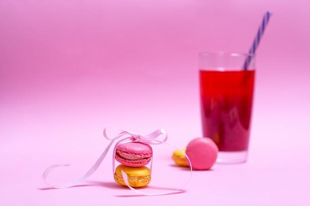 Schöne rosa und gelbe makronen werden mit band und glas fruchtgetränk im hintergrund gebunden