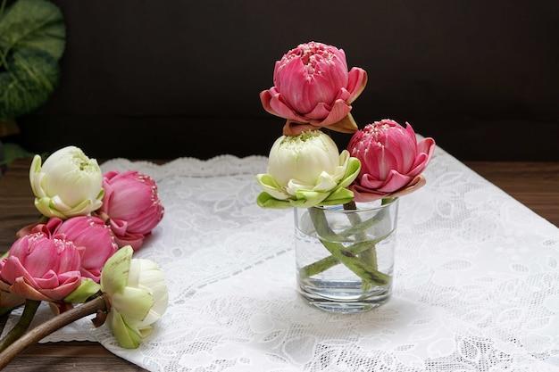 Schöne rosa und weiße lotusblume in einem glas auf dem tisch zum beten von buddha