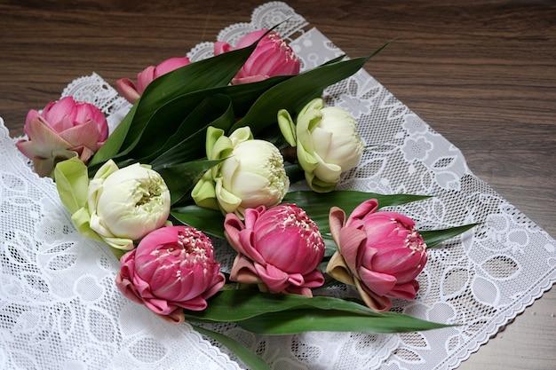 Schöne rosa und weiße lotusblume zum beten von buddha auf holzuntergrund