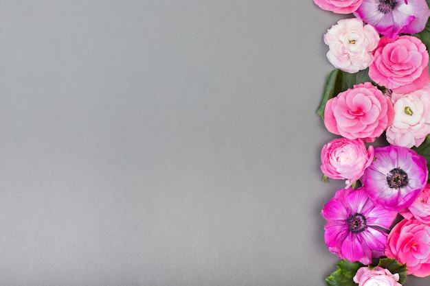 Schöne rosafarbene und weiße blumen auf grauem hintergrund. blumengrenze. pastellfarbe. grußkarte zum valentinstag oder frauentag. kopieren sie platz für text.