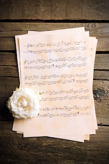 Schöne rose auf notenblättern auf holz