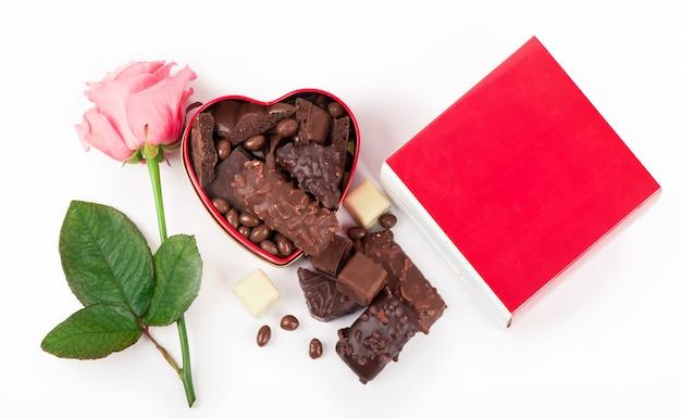 Schöne rose und dunkle schokolade für valentinstag auf isoliertem weißem hintergrund.