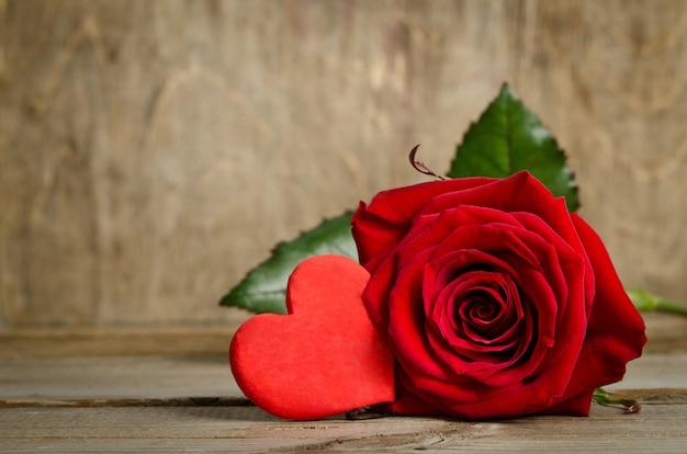 Schöne rose und ein handgemachtes herz auf der holzbrettoberfläche. herz aus salzteig
