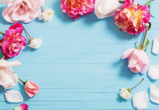 Schöne rosen auf blauem holzhintergrund