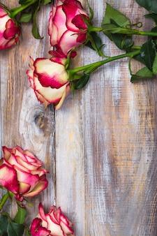 Schöne rosen auf hölzernem hintergrund. valentinstag oder muttertagesgrußkarte