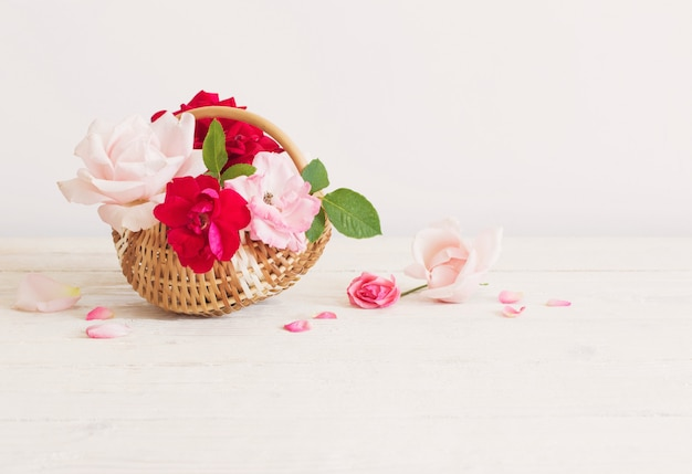Schöne rosen im korb auf holztisch