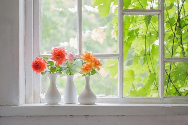 Schöne rosen in vasen auf altem holzfensterbrett