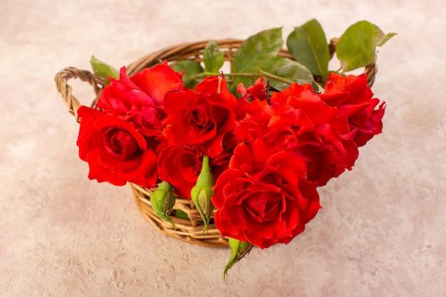 Schöne rote blumen der draufsicht der roten rosen innerhalb des korbs lokalisiert auf tisch und rosa