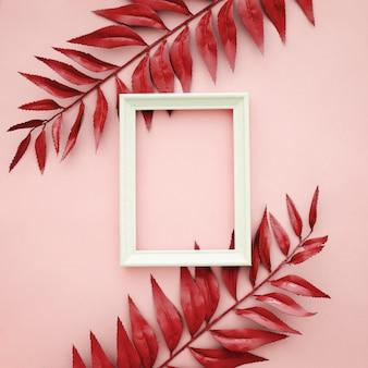 Schöne rote grenze verlässt auf rosa hintergrund mit leerem rahmen
