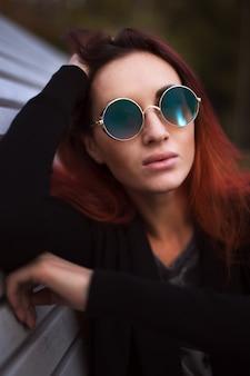 Schöne rote haarfrau in der sonnenbrille