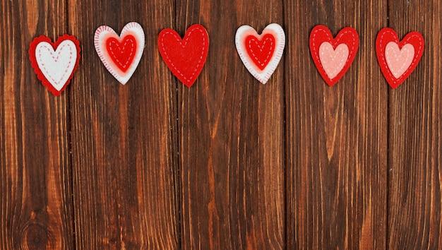 Schöne rote herzverzierungen auf einem hölzernen hintergrund auf liebhabern
