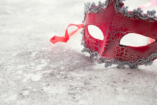 Schöne rote karnevalsmaske für karnevalsfeiertagshintergrundkonzept auf stein