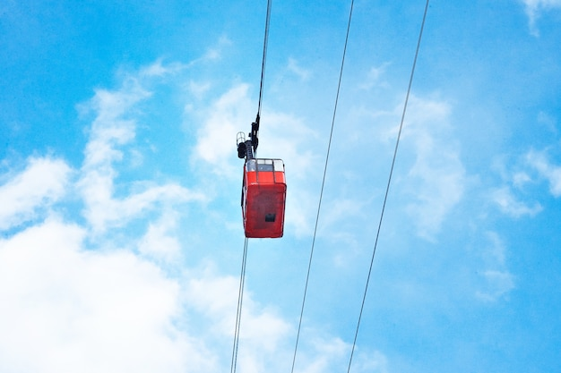 Schöne rote luftzugbahnkabine der weinlese, die über, lokalisiert auf hellblauem himmel bewegt
